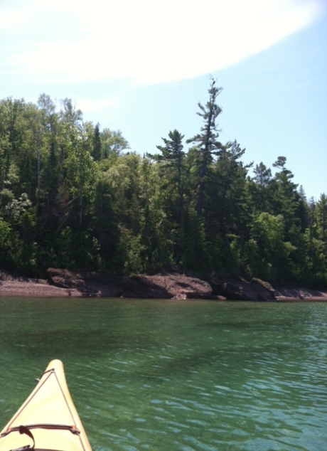 kayak approaching the wooded shore of lake superior